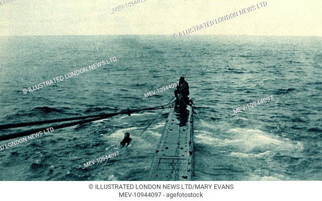 WW1 - A British marine seen saving the life of a German sailor belonging to a war-ship sunk in the North Sea. The marine is hauling the man on board using a...