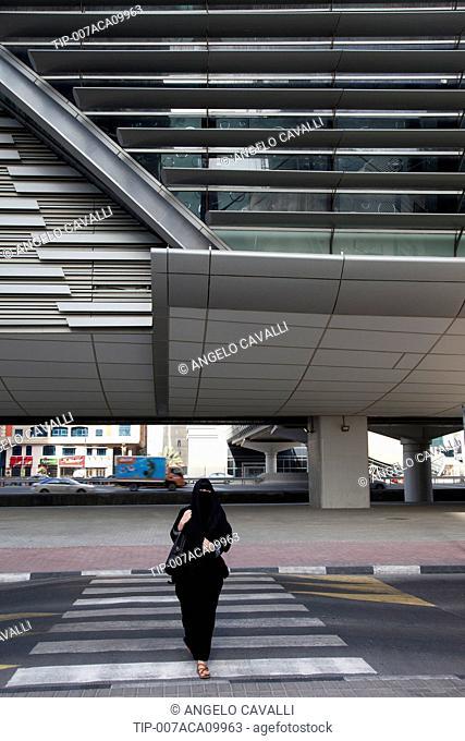 United Arab Emirates, Dubai, Arab Woman in a Hijab Crossing Crosswalk