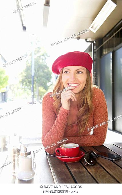 Mixed race woman having coffee at sidewalk cafe