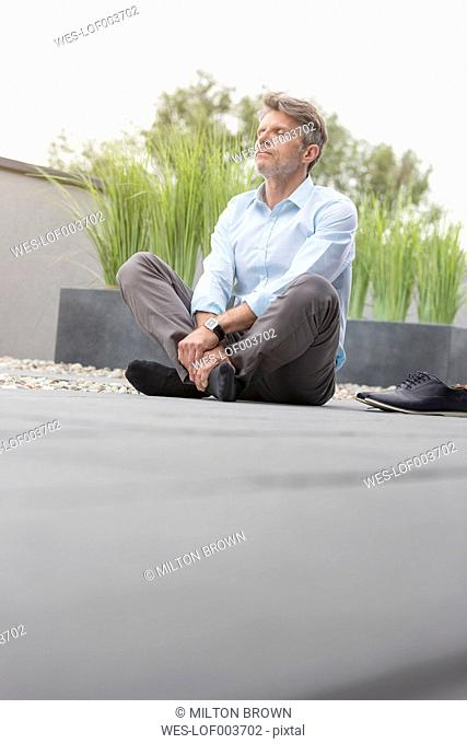 Mature man taking a break on rooftop terrace