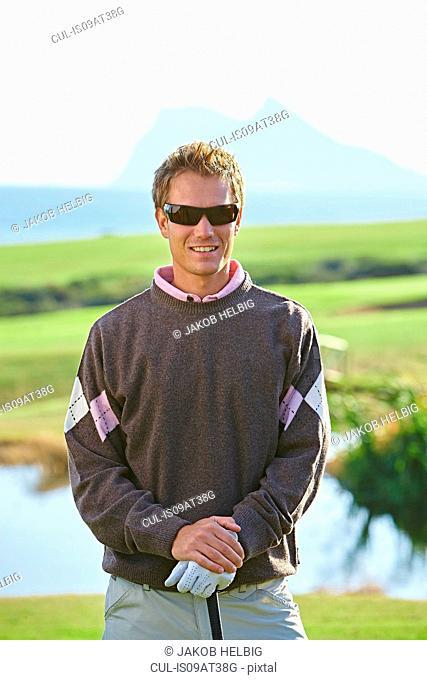 Golfer wearing sunglasses looking at camera smiling