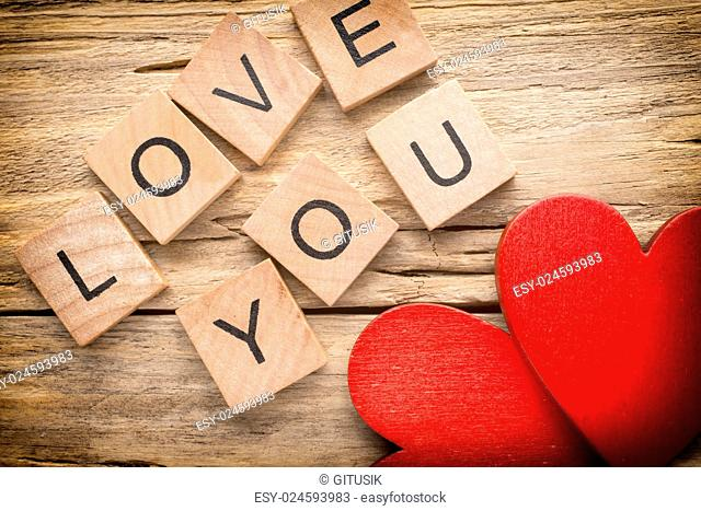 Red heart on old wooden background - Stock Image. I love you, cast out of wood kubik