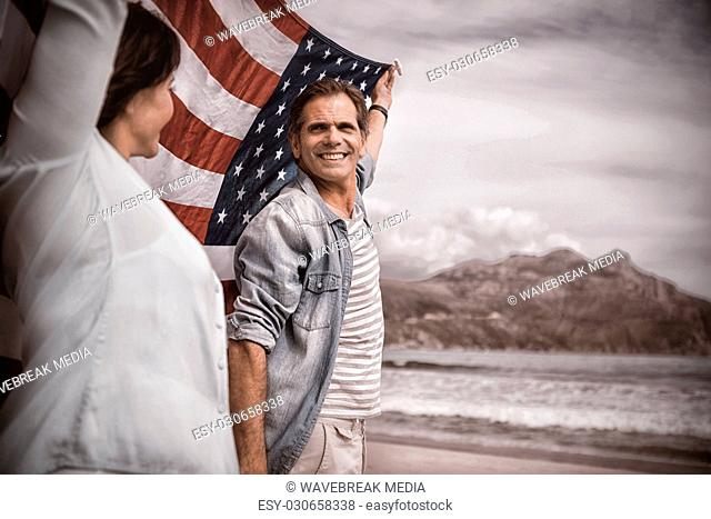 Mature couple holding American flag on beach