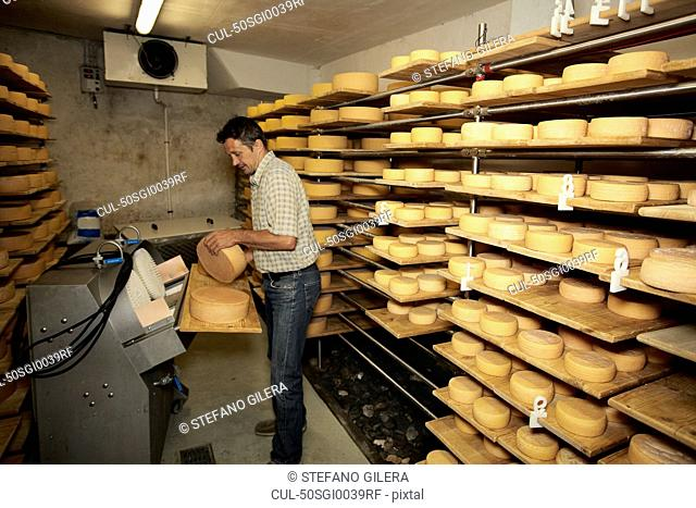 Worker finishing wheel of cheese in shop