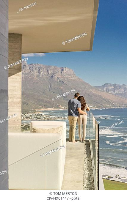 Couple looking at sunny ocean and mountain view from luxury balcony