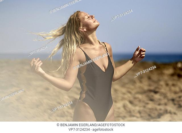 Woman at beach, sensual, shaking hairs, daydream, getting away from it all, summer. Malia, Crete, Greece
