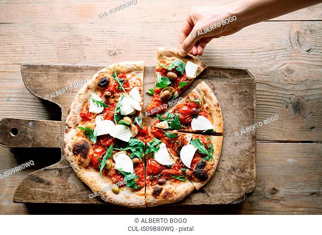 Woman taking pizza slice from pizza on chopping board, overhead view