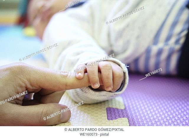 Baby holding hand of father, Valencia