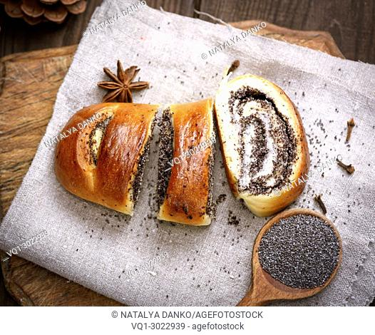 baked roll with poppy seeds on a wooden board, top view