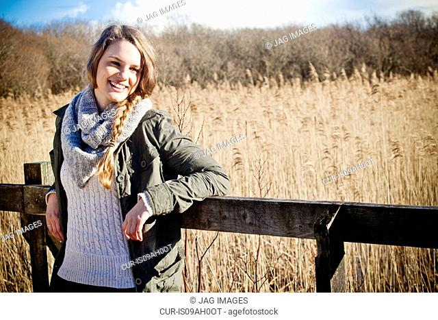 Portrait of young woman leaning against fence