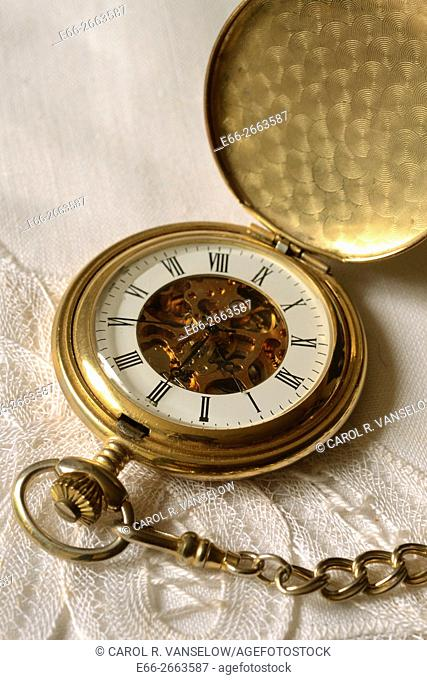 Open gold pocket watch lying on white linen and lace background
