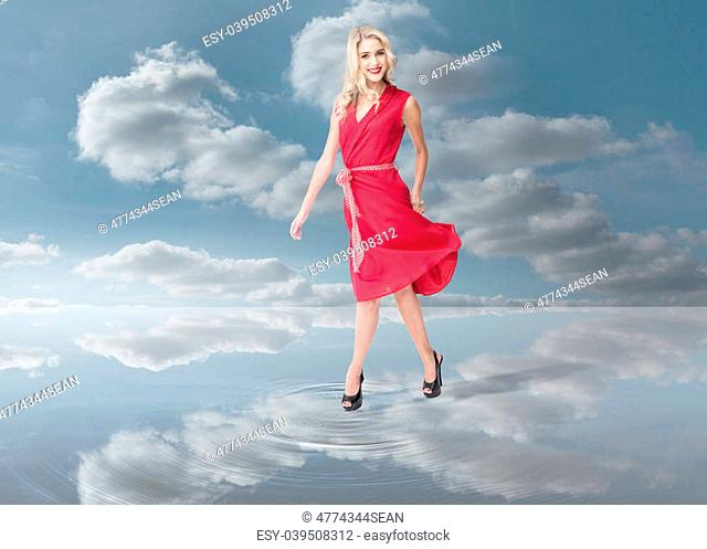 Fashion woman wearing a red dress and walking on a puddle