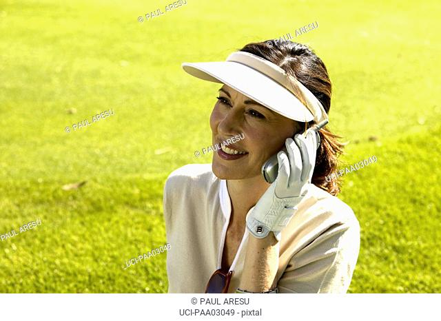 Female golfer talking on cell phone