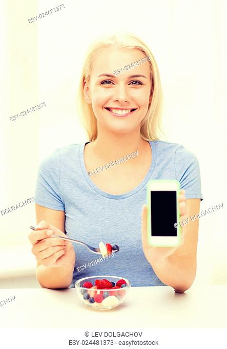 healthy eating, dieting and people concept - smiling young woman eating fruit salad and showing blank smartphone screen at home