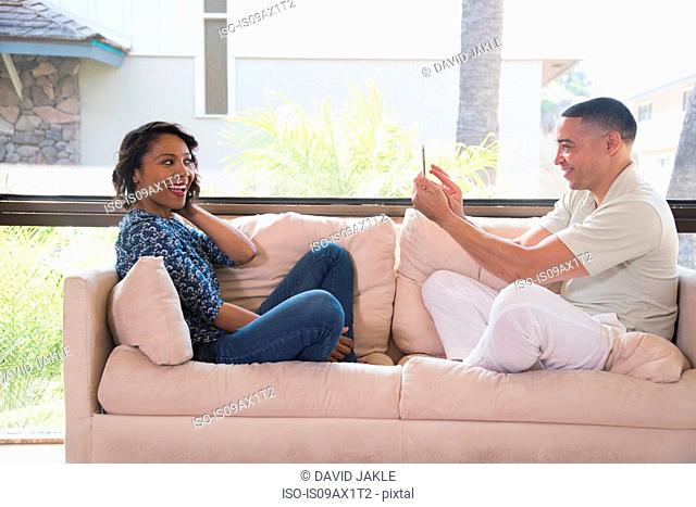 Couple taking photograph on sofa