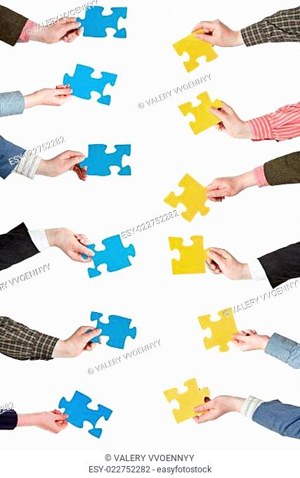 yellow and blue puzzle pieces in people hands