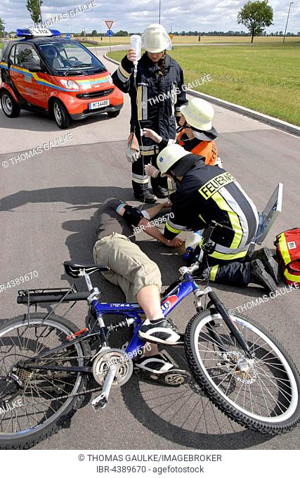 Accident, firefighters giving first aid to cyclist, Bavaria, Germany