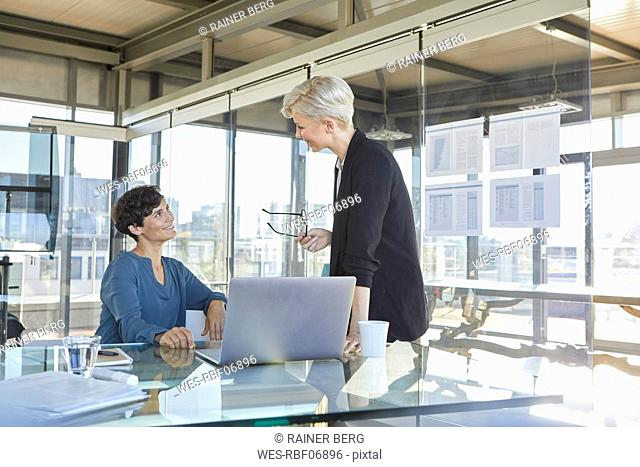 Two smiling businesswomen discussing at desk in office