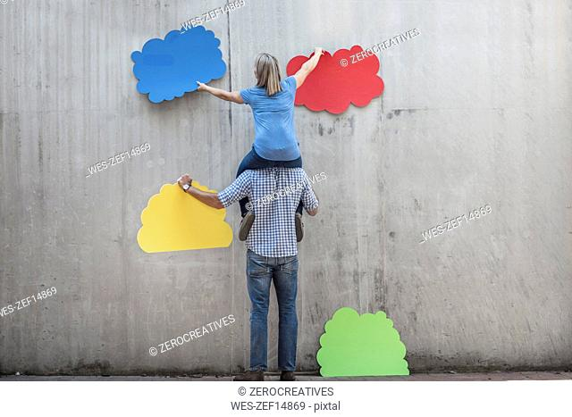 Woman sitting on a man's shoulders attaching colourful cloud shapes to concrete wall