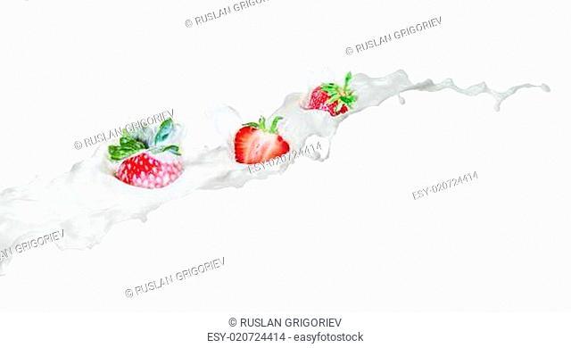 Strawberry falling into splashing milk. Isolated on white