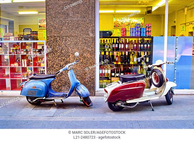 Two vintage Vespa scooters parked in front of a grocery store. Barcelona, Catalonia, Spain
