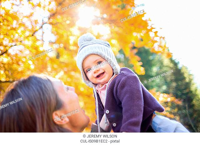 Mother holding up smiling baby girl