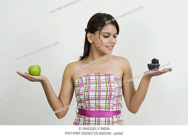 Woman holding a cup of ice cream with a green apple