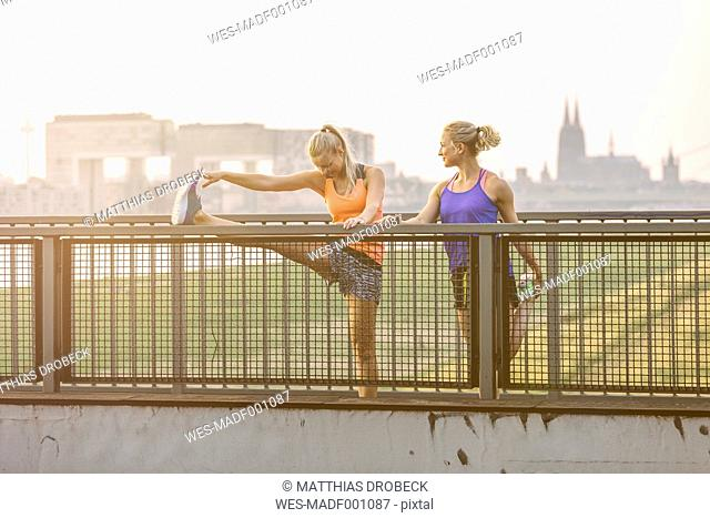Two young women stretching on bridge