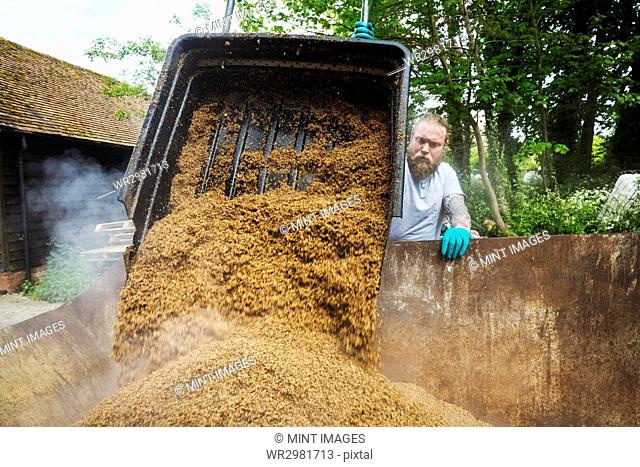 Man pouring spent grain into a large container, steam rising, during the brewing process