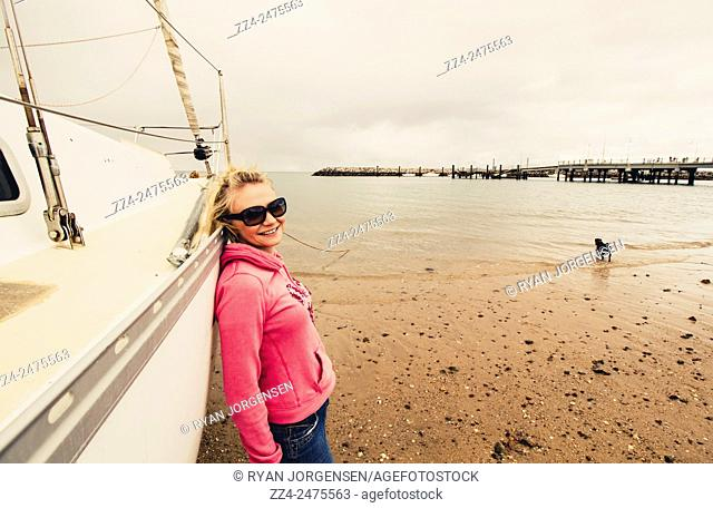 Happy summer holiday picture of a smiling blond woman in 20s lazing by a sailing boat with dog on Queensland Beach. Location: Redcliffe, Australia