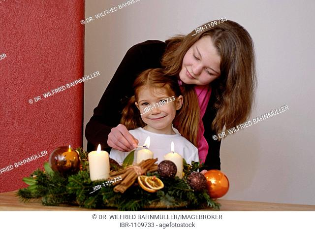 Young woman and her daughter are lighting candles on an advent wreath