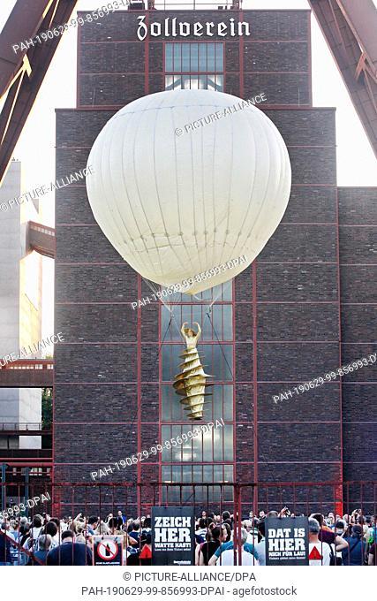 "29 June 2019, North Rhine-Westphalia, Essen: An artist of the troop """"Lufttanz"""" hangs on a helium balloon during the extra shift at Zeche Zollverein"