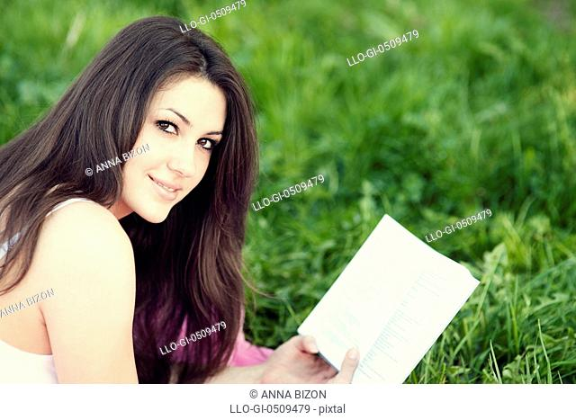 Young woman reading a book on meadow Debica, Poland
