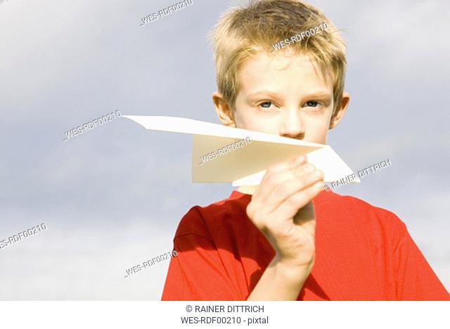 Boy 10-12 holding paper plane