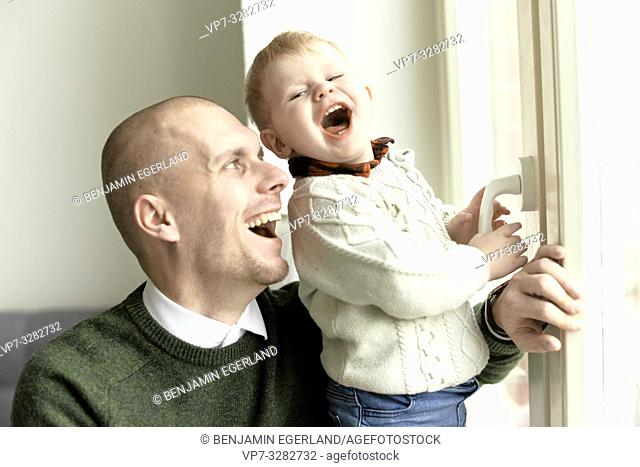 happy father laughing with baby toddler child at home, in Cottbus, Brandenburg, Germany
