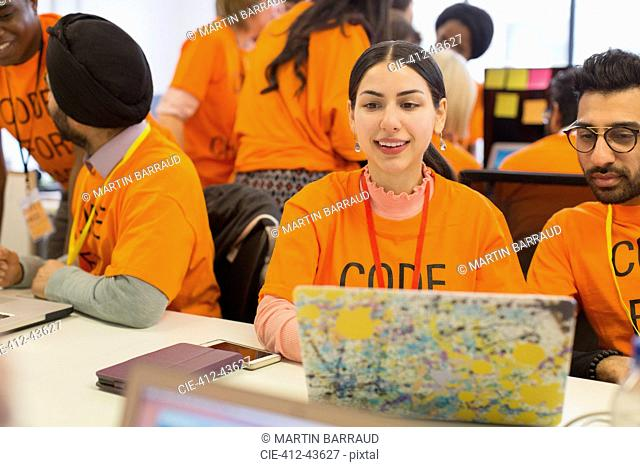 Hackers at laptop coding for charity at hackathon