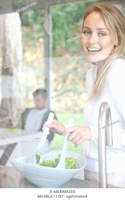 Smiling Woman Tossing Salad
