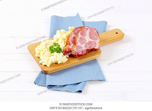 smoked pork with potato salad on wooden cutting board