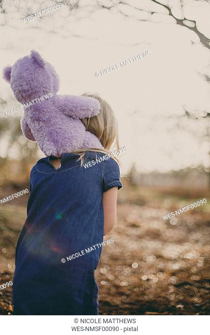 Girl carrying a teddy on her shoulders
