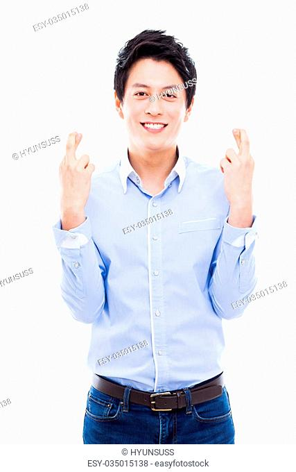 Young asian man showing lucky sign isolated on white background