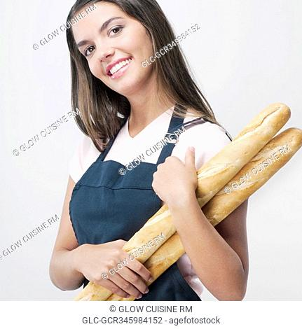 Woman holding baguettes and smiling
