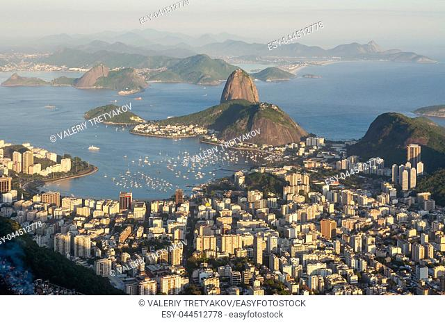 Late evening view over Rio de Janeiro from the Christ the Redeemer statue on top of Corcovado mountain. Favela in the lower left corner in the shade