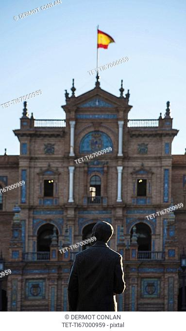 Spain, Andalusia, Seville, Facade with spanish flag and statue of Anibal Gonzales in Plaza de Espana