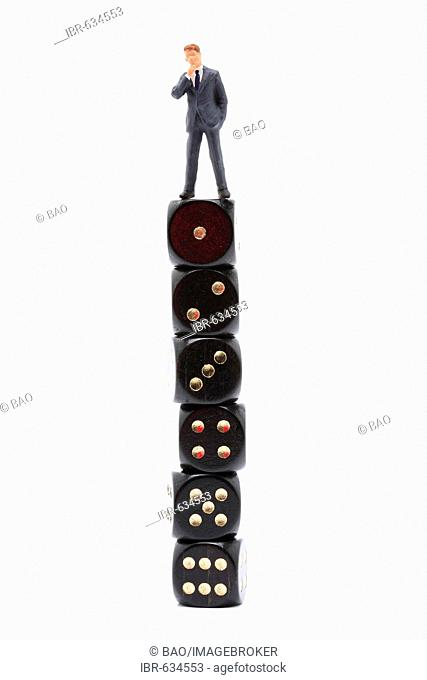Small man standing on a large stack of dice: symbol for success