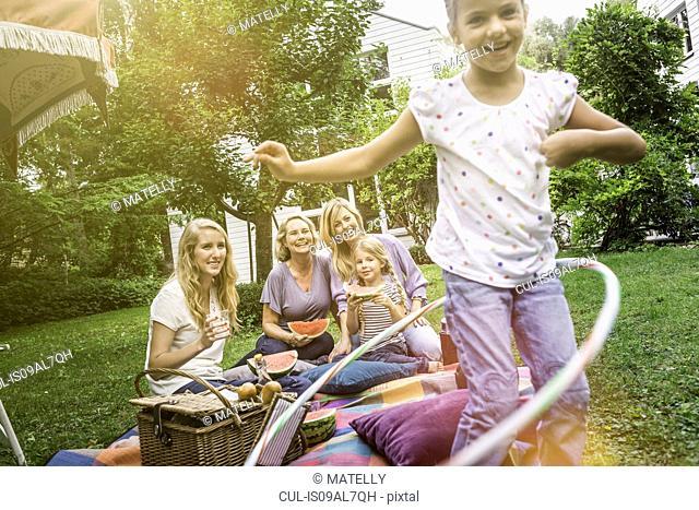Girl playing with hula hoop at family picnic