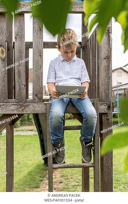 Little boy sitting on playgroung equipement looking at digital tablet
