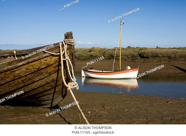Boats moored on the river at Blakeney, Norfolk, England