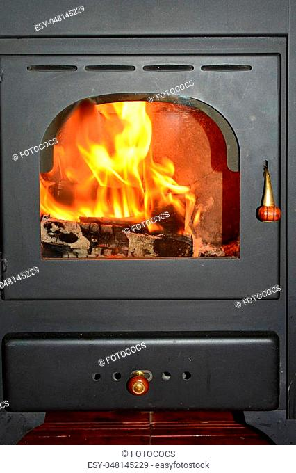 Old wood stove with firewood burning inside, close up view
