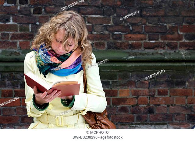 young woman in a coat sitting in front of a red brick wall reading a book