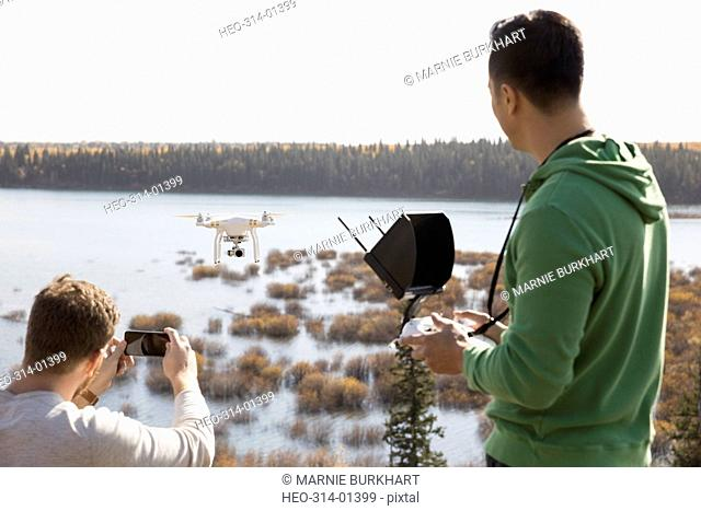 Male friends with drone equipment and camera phone overlooking lake